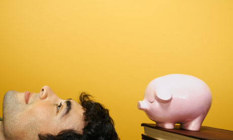 Young man next to a piggy bank