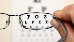 Looking through glasses at an eye exam chart